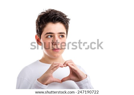 Caucasian young boy with acne-prone skin. in a white long sleeved t-shirt smiles making hand heart gesture - stock photo