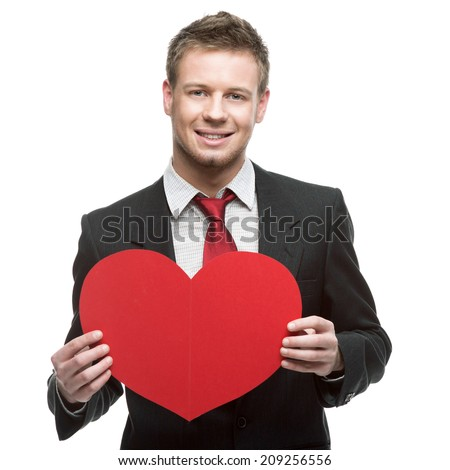 caucasian young businessman in gray suit holding sign in form of big red heart . isolated on white - stock photo