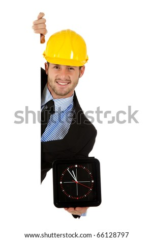 Caucasian young businessman wearing yellow helmet, behind a wall holding black, square clock . Copy space. Studio shot. White background. - stock photo