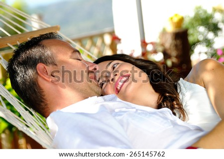 Caucasian young couple dressed in white on a rope hammock on the terrace of a country house lovingly looking lateral view - stock photo