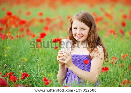Caucasian young female holding a glass of water in a flower field - stock photo