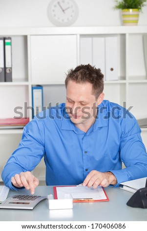 Caucasian young male accountant smiling while calculating the profit of a successful business, at his desk, in the office