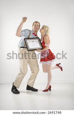 Caucasian young man dressed like nerd cheering and receiving kiss and certificate from Caucasian young blonde woman dressed in french maid outfit. - stock photo