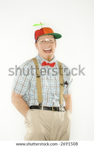 Caucasian young man dressed like nerd wearing propeller cap with hands in pockets looking at viewer with big smile. - stock photo