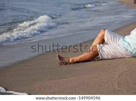 Caucasian young man, in casual clothing, sitting on beach in the sunrise light.