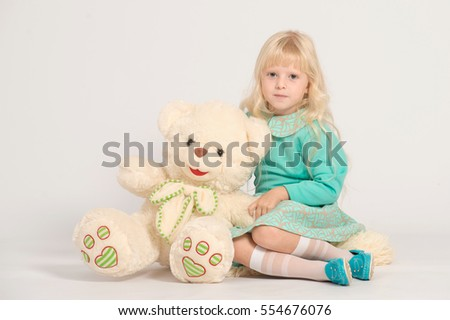 Caucasian young smiling blondy girl in light green dress sitting with white teddy bear looking to the camera