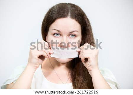 Caucasian young Woman glues tape her mouth in protest, grey background - stock photo