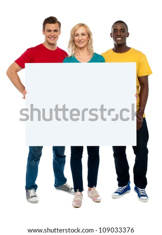 Caucasian young woman showing white adverting board while two guys standing beside her - stock photo