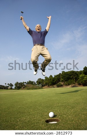 Caucasion mid-adult man holding golf club jumping in air cheering with golfball and hole in foreground. - stock photo