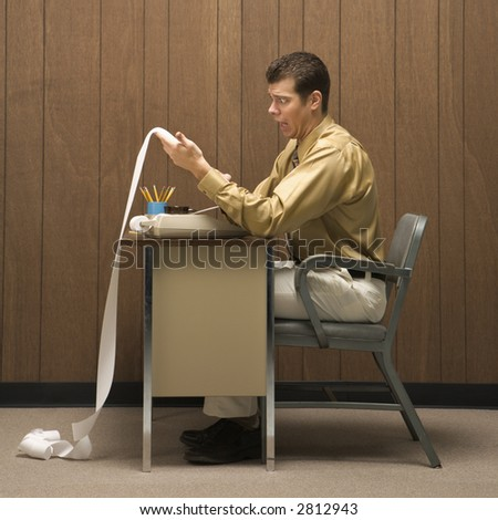 Caucasion mid-adult retro businessman sitting at desk looking with shocked expression at long adding machine printout that reaches all the way to the floor.