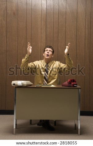 Caucasion mid-adult retro businessman sitting at desk raising hands in air with look of frustration.