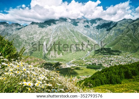 Caucasus mountains, Mount kazbek  in summer green and blue sky, with village