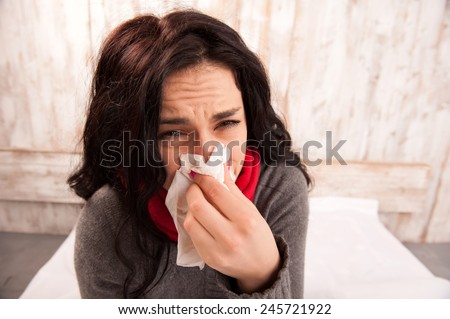 Caught a cold. Closeup image of young sick woman blowing her nose while sitting on bed against wooden wall - stock photo