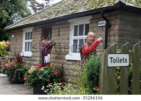 Caught short, elderly Gent dashes to pretty public Toilette in a small English Village. with some light motion blur - stock photo