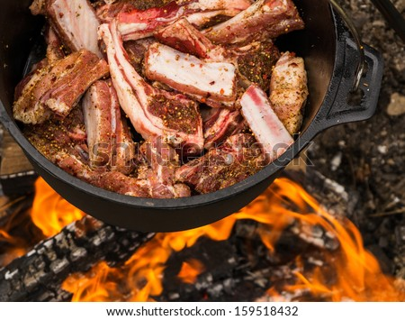 Cauldron full of lamb meat - cooking on fire - stock photo