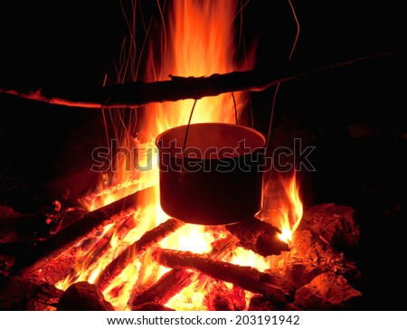 cauldron on the fire at night - stock photo