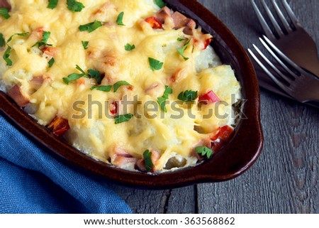 Cauliflower and cheese gratin in baking dish on rustic wooden background