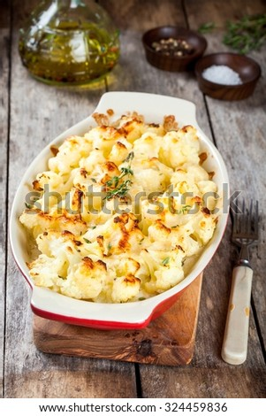 Cauliflower and cheese gratin in the baking dish on wooden table - stock photo