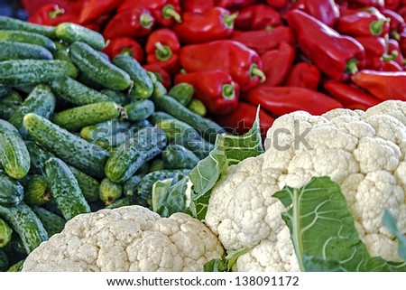 Cauliflower, cucumbers and red peppers exposed to sale in bulk in a market. - stock photo