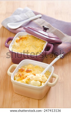 cauliflower gratin with cheese in ceramic cocotte on the board of bamboo - stock photo