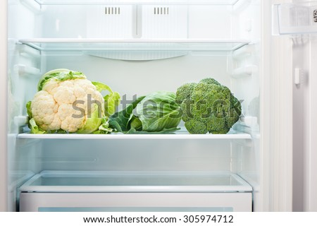 Cauliflower, green cabbage and green broccoli on shelf of open empty refrigerator. Weight loss diet concept. - stock photo
