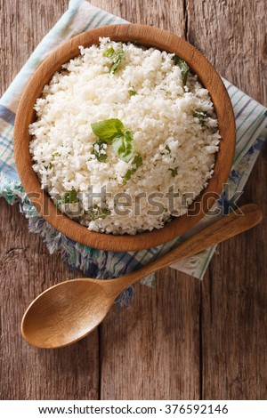 Cauliflower rice with basil close up in a bowl on the table. Vertical top view - stock photo