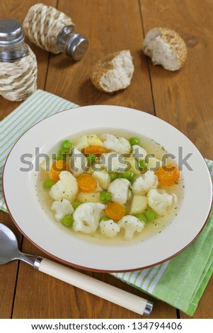 Cauliflower soup with green peas in a bowl on a wooden table