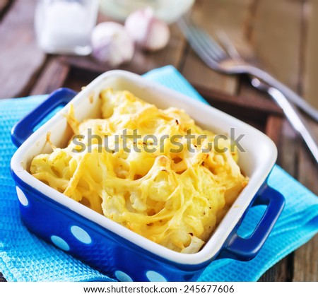cauliflower with cheese in bowl and on a table - stock photo