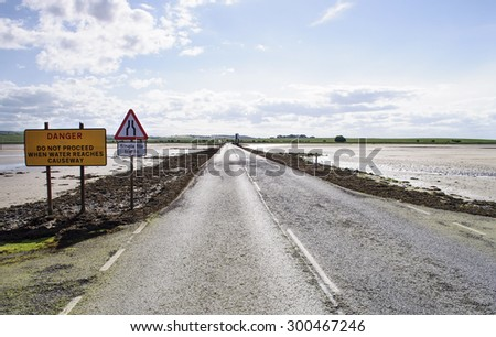 causeway with roadsigns - stock photo