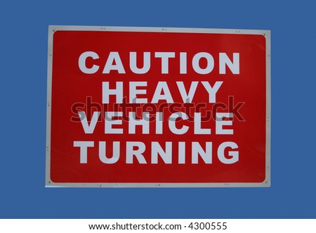 caution heavy vehicles turning sign on blue - stock photo