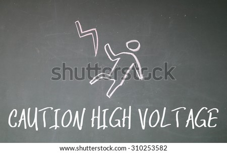 caution high voltage text write on blackboard - stock photo