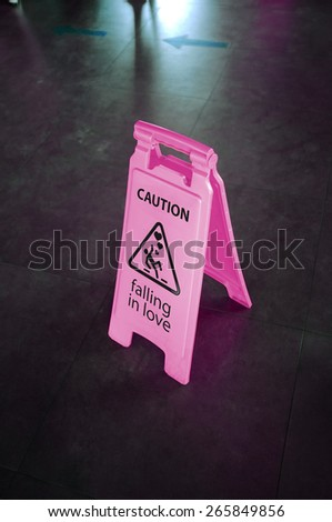 Caution pink sign for warning, falling in love, on a floor - stock photo