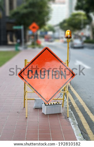 Caution road street sign with defocused street in background - stock photo
