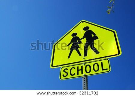 Caution school sign, blue sky - stock photo
