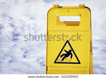 caution slippery floor sign at an entrance in winter - stock photo