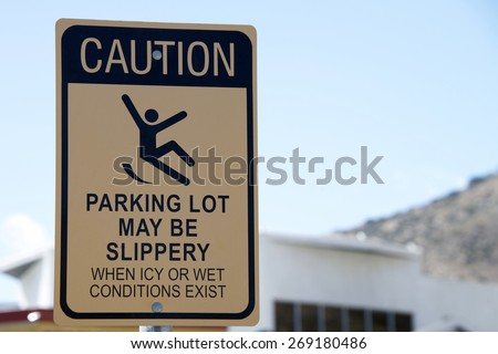 Caution, Slippery when wet sign in a parking lot. Warning patrons - stock photo
