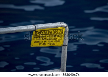 caution swiimming with sharks is not advised remain in your cage at all time yellow warning sign - stock photo