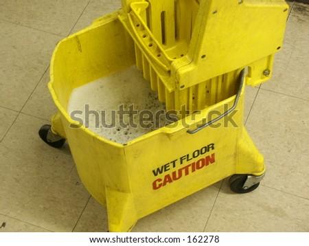Caution Wet Floor Sign and Mop Bucket - stock photo