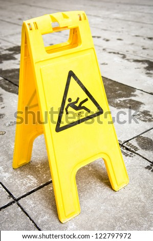caution wet floor sign at a sidewalk - stock photo