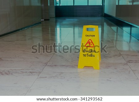 caution wet floor sign inside building in early morning with light reflection through green glass wall behind