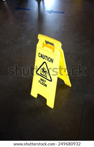 Caution yellow sign for wet floor warning on a floor