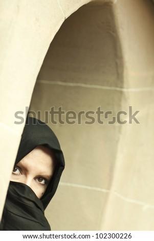 Cautious Islamic Woman in a Window Pane Wearing Traditional Burqa or Niqab. - stock photo