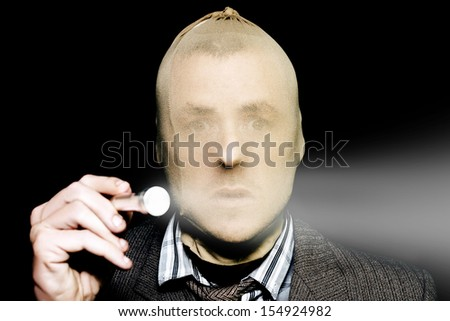 Cautious male burglar with a stocking over his head shining a narrow beam torch in front of him in the darkness to light the house interior in a home burglary concept on black background - stock photo
