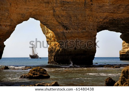 cave beach and a boat in algarve, the south of portugal, Marinha beach - stock photo