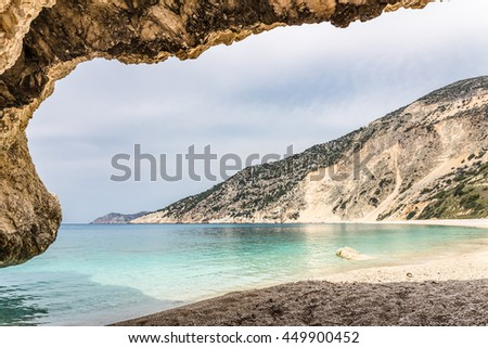 Cave outlook on cove with  sea mountain and gravel beach - stock photo