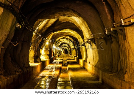 cave tunnel mine long walk way with light  - stock photo