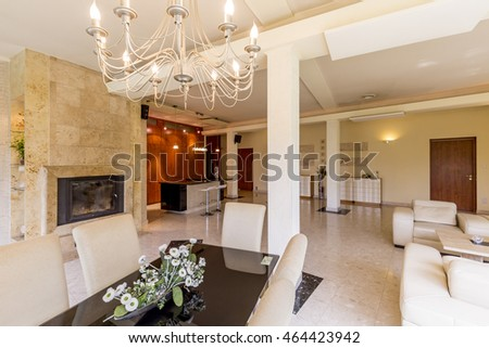 Cavernous interior of a luxurious dining room linked with lounge room and kitchen