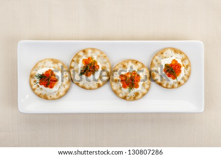 Caviar appetizer with goat cheese and crackers on white plate from above - stock photo