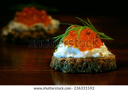caviar canapes, red, with dill garnish on dark brown wood, one party snack blurred in the background - stock photo