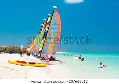 CAYO SANTA MARIA, CUBA - JULY 16, 2014 : Tourists enjoy the beautiful beach with colorful sailboats - stock photo